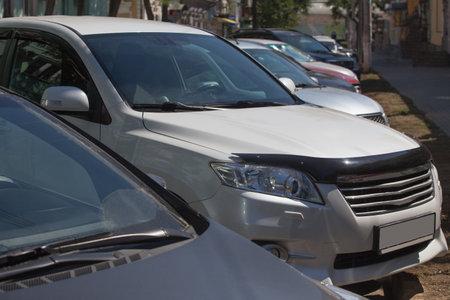 Cars parked on city street on summer day. Standard-Bild