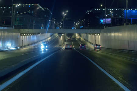 Car traffic at night in a tunnel on a two-tier junction in the city.