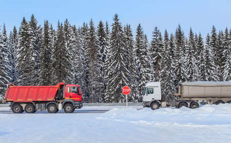 Trucks move on a snowy winter road in the opposite direction along the forest
