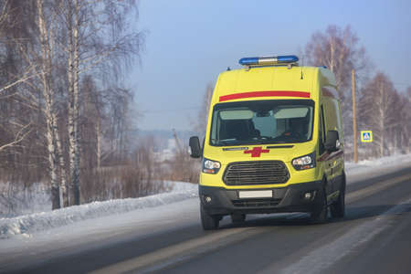 ambulance car moves along a country road in winter. Standard-Bild