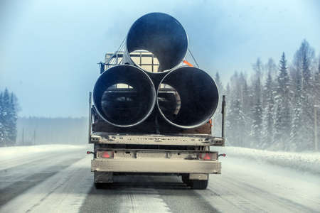 truck transports large-diameter pipes for a gas pipeline on a winter snow-covered road. Standard-Bild