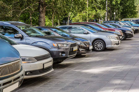 Cars in the parking lot on the street near the park Standard-Bild