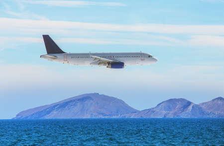 passenger plane flies over a mountain sea coast