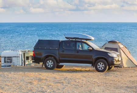 Car, camper, tent on the seashore on camping in summer Standard-Bild