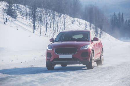 SUV moves in the winter on a country road in the mountains