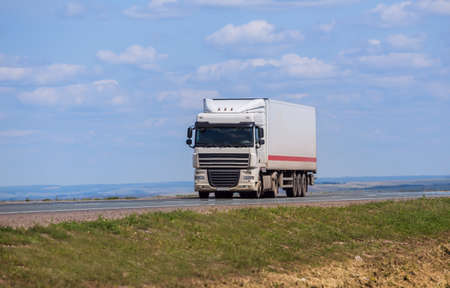 white truck transports freight on the country highway Standard-Bild