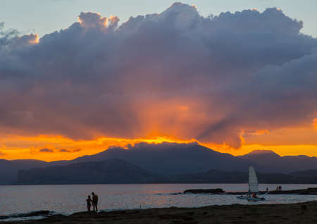 Beautiful sunset over the mountains by the sea. A guy and girl are watching sailing yacht moving on the water
