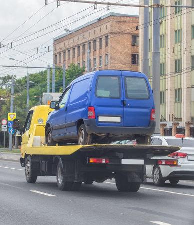 tow truck is transporting broken car along city street.