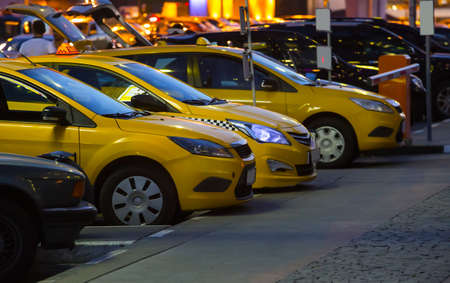 Yellow taxi cars at night in parking in city center.