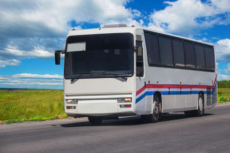 Tourist bus moves along a country road on summer sunny day