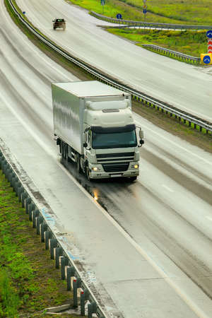 truck moves on wet highway outside city after rain in spring. Standard-Bild