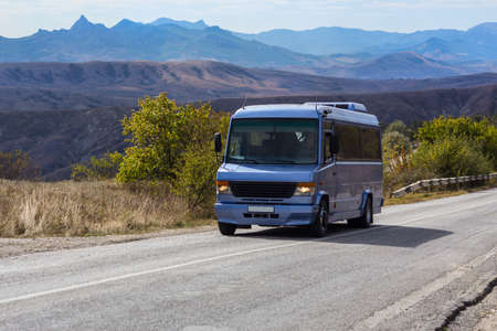 Bus moves along the road against the backdrop of a beautiful mountain landscape