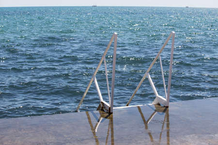 Ladder with handrails to the water on the sea on the pier