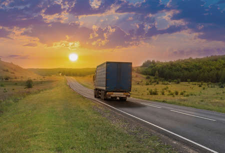 Truck moves along a suburban highway at sunset in summer. Standard-Bild