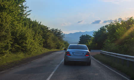 car moves on a road in the mountains on a summer day Standard-Bild