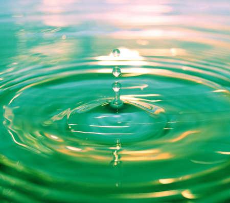 Drops fall in green water photo