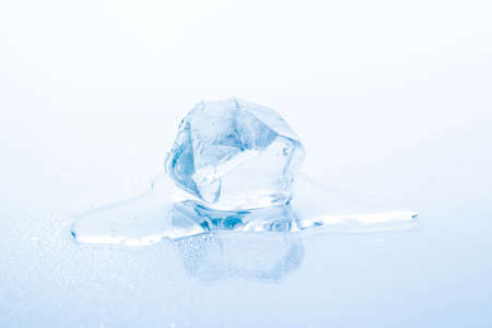 Cube of frozen ice is melting isolated on white background