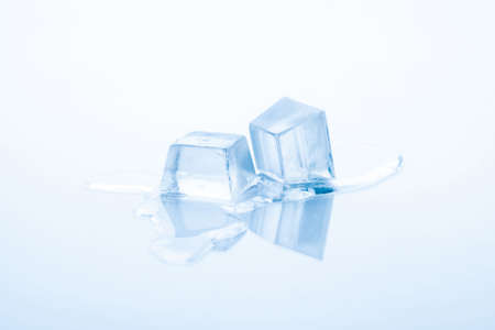 Two cubes of frozen ice are melting isolated on white background