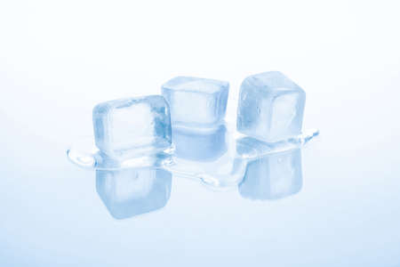 Three cubes of frozen ice are melting isolated on white background