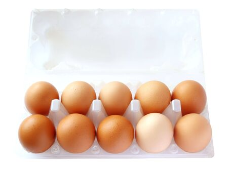 Ten of brown eggs in packing on a white background photo