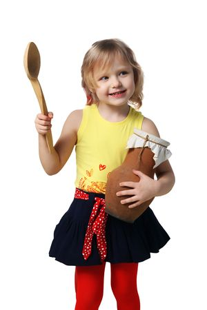 Little girl with a wooden spoon and crock on a grey background Stock Photo