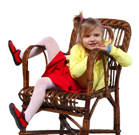 Little girl in a wicker chair on a white background photo