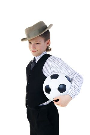 Boy in a grey hat and in a black suit and by soccer ball on a white background photo