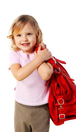 Little girl with a red bag on a grey background. (isolated) photo