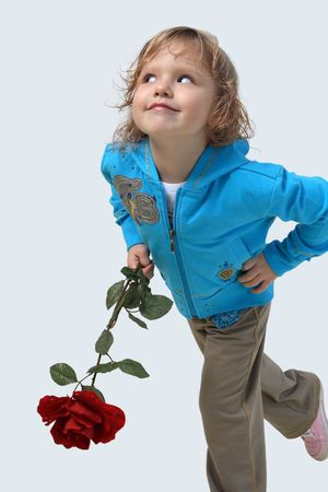 Little girl with a red rose on a grey background photo
