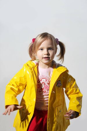 Little girl in a yellow jacket on a grey background photo