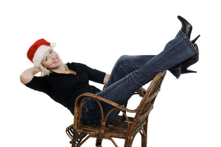 Young girl in a Santa Claus hat in a wicker chair on the white background photo