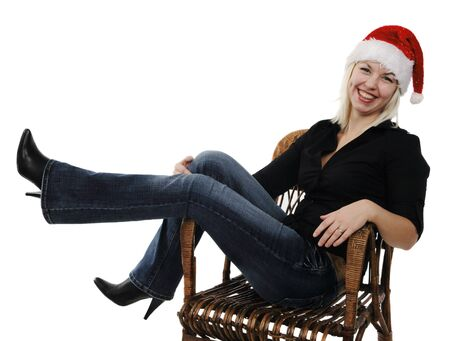 Young girl in a Santa Claus hat in a wicker chair on the white background Stock Photo - 6059168