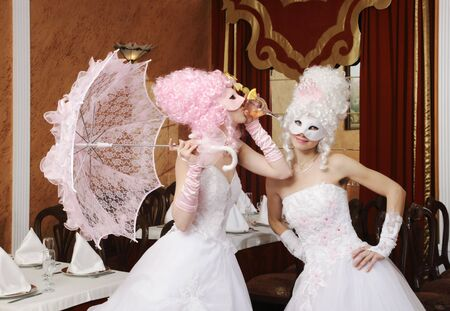 Two girls in wedding dresses and masks photo