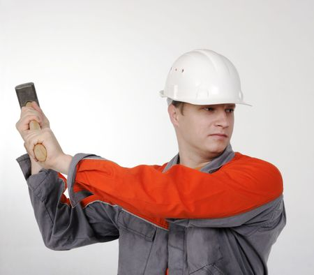 man in overalls with a hammer in his hands, the builder on the grey background photo