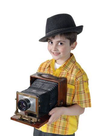 Little boy with an old camera on the white background photo