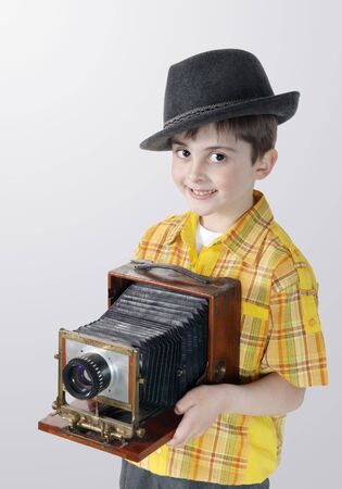 Little boy with an old camera on the grey background photo