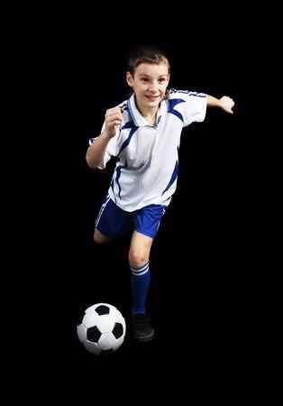 world player: Ni�o con bal�n de f�tbol, futbolista sobre el fondo negro. (aislado) Foto de archivo