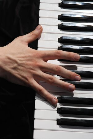 Hands above keys of the piano. A photo close up  photo