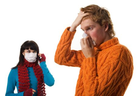 ah1n1: Man influenza patients, a woman stands behind a mask, said by telephone, A(H1N1), on the white background. Focus is on the syringe