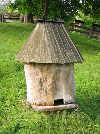 Old wooden bee hive on a background of green grass photo