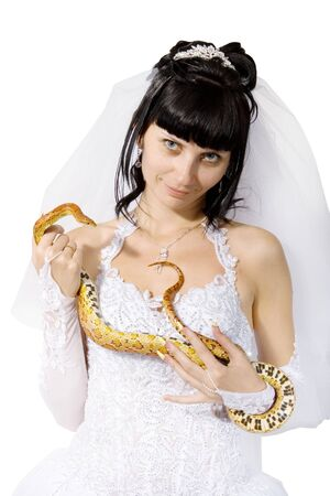 bride in a white dress with a snake boa in his hands photo
