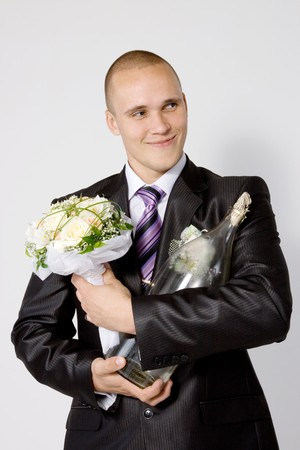 fellow: Young fellow, fiance, with a nosegay and bottle of vodka on the white background