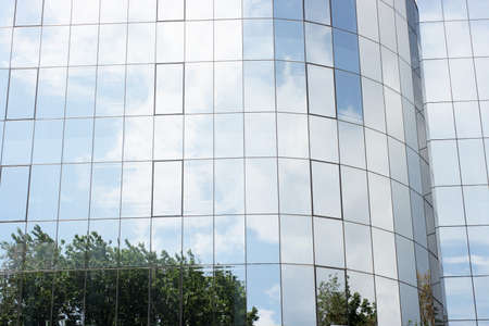 modern building glass reflects nature of trees and clouds photo