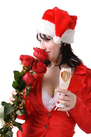 Portrait of a beautiful young woman in a red suit and hat of Santa Claus with red roses and champagne on the white background photo