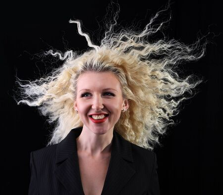 Pretty curly blonde on a black background. Hair in the wind Stock Photo - 8421405