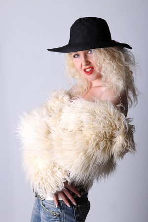 Curly blonde in a black hat and white fluffy fur coat Stock Photo - 8421406
