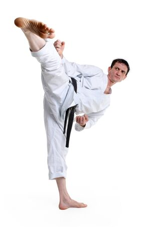 hits: Karate. Man in a kimono hits foot on the white background Stock Photo