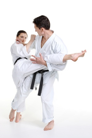 Karate. Young girl and a men in a kimono with a white background. Battle sports capture photo
