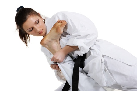 jujitsu: Karate. Young girl in a kimono with a white background. Sportswoman doing sports capture Stock Photo