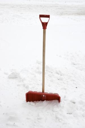heap snow: red snow showel burried in heavy snow  Stock Photo